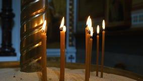 Tunna stearinljus som bränner i kyrkan arkivfilmer