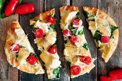 Tunnbrödpizza med mozzarellaen, tomater, spenat, kronärtskockor, över lantligt trä royaltyfri fotografi