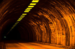The Tunnel. Tunnel, sidewalk, roadway and lights leading to a far away exit Royalty Free Stock Image