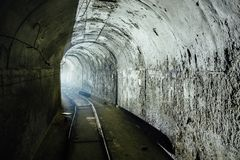 Cargo tunnel in abandoned soviet bunker with railway. Turn the tunnel. Light from the turn. Tunnel in abandoned soviet bunker with railway. Turn the tunnel Stock Photo