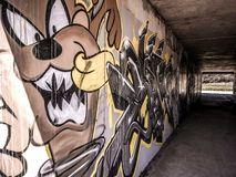 Tunnel Art Graffiti. Street Art Graffiti of Brown Speedy Happy and hungry looking Tasmanian Devil with his toothy grin, painted in concrete tunnel. Canberra royalty free stock photo