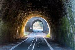 Tunnel BRITANNIQUE foncé de route sur le coucher du soleil photographie stock libre de droits