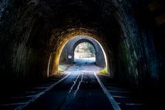 Tunnel BRITANNIQUE foncé de route sur le coucher du soleil photos stock