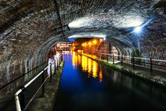 Tunnel in the city center of Birmingham, UK. Birmingham, UK. Tunnel in the city center during the rain, illuminated buildings at night, famous Birmingham canal Royalty Free Stock Photos