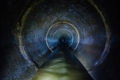 Tunnel concret rond d'égout souterrain d'obscurité Conduit d'égout débordant de jet d'eaux usées industrielles et d'eaux d'égout  images libres de droits