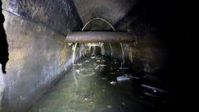 Tunnel concreto scorrente della fogna sotterranea scura del tiro delle acque luride urbane e dell'acqua di scarico industriale stock footage