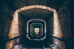 Tunnel de brique ou couloir et lumière souterrains ruinés d'extrémité, de manière abstraite d'espérer ou s'échapper à la liberté Images stock