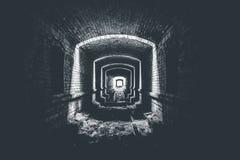 Tunnel de brique ou couloir et lumière souterrains ruinés dans l'extrémité, manière d'espérer le concept, photo noire et blanche Photos stock