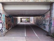 Tunnel della bicicletta con molti graffiti Fotografia Stock