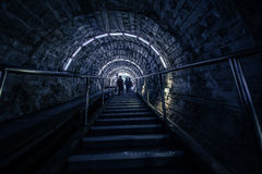 The tunnel - the descent into the mine. The flight of stairs - people are going up the steps - their silhouettes. Arched ceiling - a long narrow corridor, the Royalty Free Stock Photo