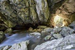 Tunnel di pietra con l'uscita Immagini Stock Libere da Diritti