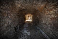 Tunnel di pietra scuro della vecchia fortezza di pietra Fotografie Stock