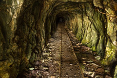 Tunnel in disused mine with rails Stock Photo