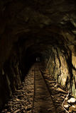 Tunnel in disused mine with rails Royalty Free Stock Image