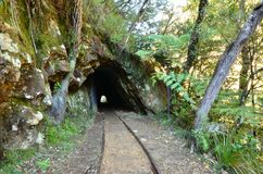 Tunnel Entrance. The entrance to an old mining tunnel with rail tracks stock image