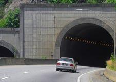 Tunnel entrance. Car entering a highway tunnel entrance through the mountain Stock Image