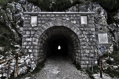 Tunnel Entrance Through a Mountain. Stone entrance to an old brick tunnel that runs through a mountainside. Horizontal shot Royalty Free Stock Image
