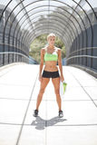 Through the tunnel. A female athlete standing under a pedestrian walkway with a cage over top Stock Images
