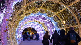 The tunnel of glowing lights. Decorating for Christmas. The tunnel of glowing lights. People walk on the streets decorated for Christmas stock footage