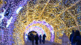 The tunnel of glowing lights. Decorating for Christmas. The tunnel of glowing lights. People walk on the streets decorated for Christmas stock video footage
