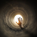 Tunnel Horror. Zombified hand rising up inside a dark tunnel Royalty Free Stock Photography