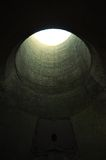 Tunnel. Light at the end of the tunnel. A round concrete opening leads to an underground chamber with a metal hatch barely visible on the furthest, dark side Royalty Free Stock Photo