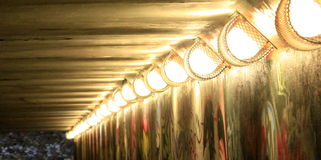 Tunnel lights. Bright tunnel lights in dark tunnel stock photos