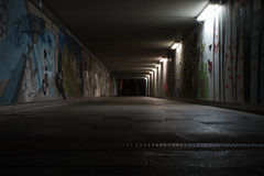 Tunnel. A tunnel in my hometown which is abandoned in the nights. The wounderful grafitti adds a interesting mood and the assymetric lights 'break' the clear Royalty Free Stock Photos