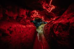 Tunnel in a natural dark creepy cave, lit by red light. Toned Royalty Free Stock Photos