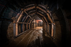 Tunnel in old coal mine, reinforced with wood. Corridor in modern coal mine, tracks and elements of internal infrastructure visible. Tunnel reinforced with wood stock images