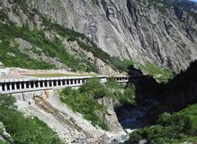 Tunnel pietroso scenico della strada in alpi svizzere in SVIZZERA vicino alla città di Andermatt con il paesaggio alpino della ga Immagine Stock