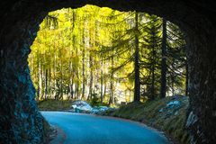 Tunnel through raw rock on an old military road headed to Mangart saddle high in Julian alps. On a sunny beautiful autumn day with colorful scenery and stock photography