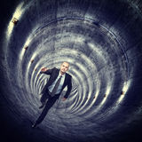 In the tunnel. Running man in concrete long tunnel Royalty Free Stock Photography