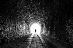 The tunnel. Silhouette of man at the end of dark long tunnel Stock Photography