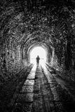 The tunnel. Silhouette of man at the end of dark long tunnel stock images