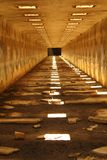 Tunnel. A subterranean service tunnel with openings at the top letting in sunlight fall in square pockets on the ground. A dark shadow at the end Royalty Free Stock Photography