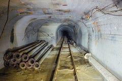 Tunnel technique avec le chemin de fer à voie étroite et la construction de la canalisation de la canalisation de chauffage Images stock