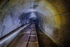 Tunnel technique souterrain inondé abandonné de mine avec le tuyau et le chemin de fer à voie étroite Image stock