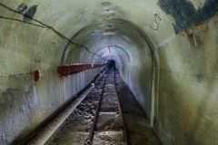 Tunnel technique souterrain inondé abandonné de mine avec le tuyau et le chemin de fer à voie étroite Images libres de droits
