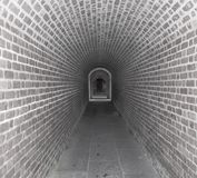 Tunnel in Time. Brick tunnel walkway through a old fort wall with slate floors Stock Photos