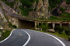 Tunnel on Transfagarasan road of Romania. Dangerous transportation scenery among the rocky cliffs in high Carpathian mountains in summer morning royalty free stock images
