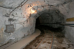 The tunnel of the underground mine. The turning tunnel with metals of the underground mine in Russia Royalty Free Stock Photos