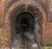 Tunnel van de gevaars de Donkere baksteen van de catacombe met overspannen ingangsmening aan de duisternis Royalty-vrije Stock Fotografie