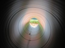 Tunnel View. Red and brown sandy earth outside the pipe give this tunnel view its reddish cast. These pipes are part of a new natural gas pipeline track in Stock Images