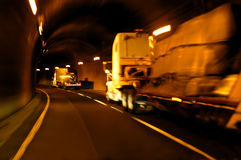Tunnel Vision. Two 18 wheelers speed through a tunnel carrying their cargo to its destination.  Tunnel is dark and is lit by inwall lights.  Trucks are blurred Royalty Free Stock Photo