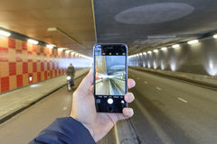 Tunnel vision. A hand holding a Cell phone taking a picture of a tunnel in the netherlands Royalty Free Stock Photo