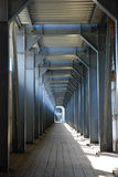 Tunnel walk through construction site. Endless tunnel walkside with light in the end Stock Image