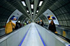 Pedestrian tunnel. Tunnel at Waterloo station, London, with commuters on escalator Royalty Free Stock Photography