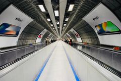 Pedestrian tunnel. Tunnel at Waterloo station, London, with commuters on escalator Stock Photos
