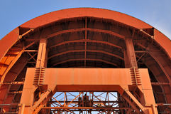 Tunnel working equipment in arch shape. Tunnel working construction equipment under blue sky, shown as featured structure, arch shape and orange color Royalty Free Stock Images